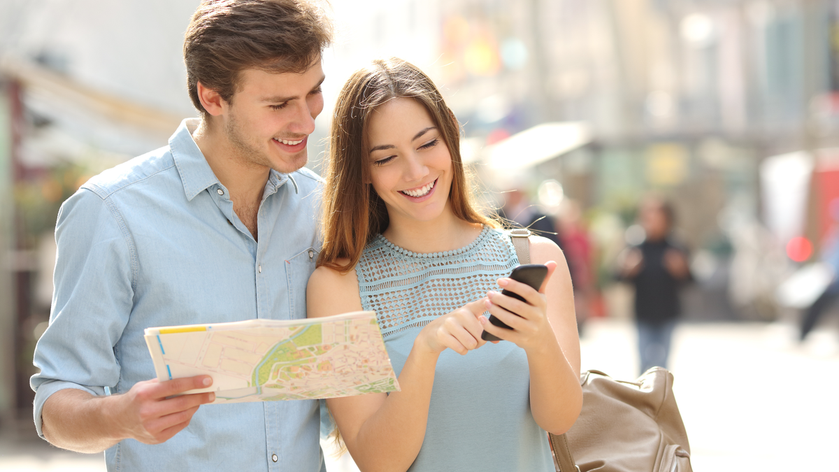 Couple of tourists consulting a smartphone app guide to plan their adventure
