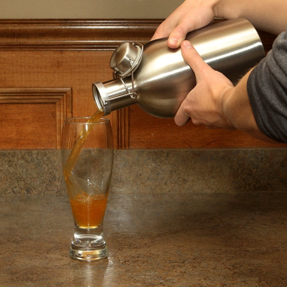 Someone pouring beer from a steel beer growler into a beer glass