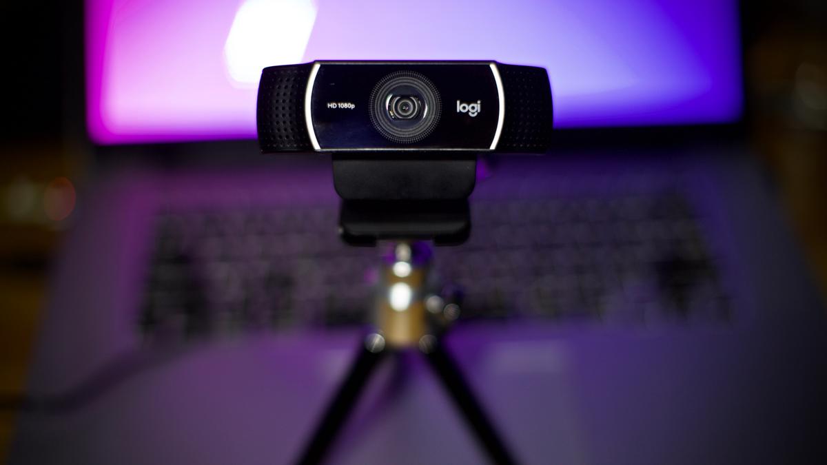 a Logitech webcam on small desktop tripod in front of colorful screen