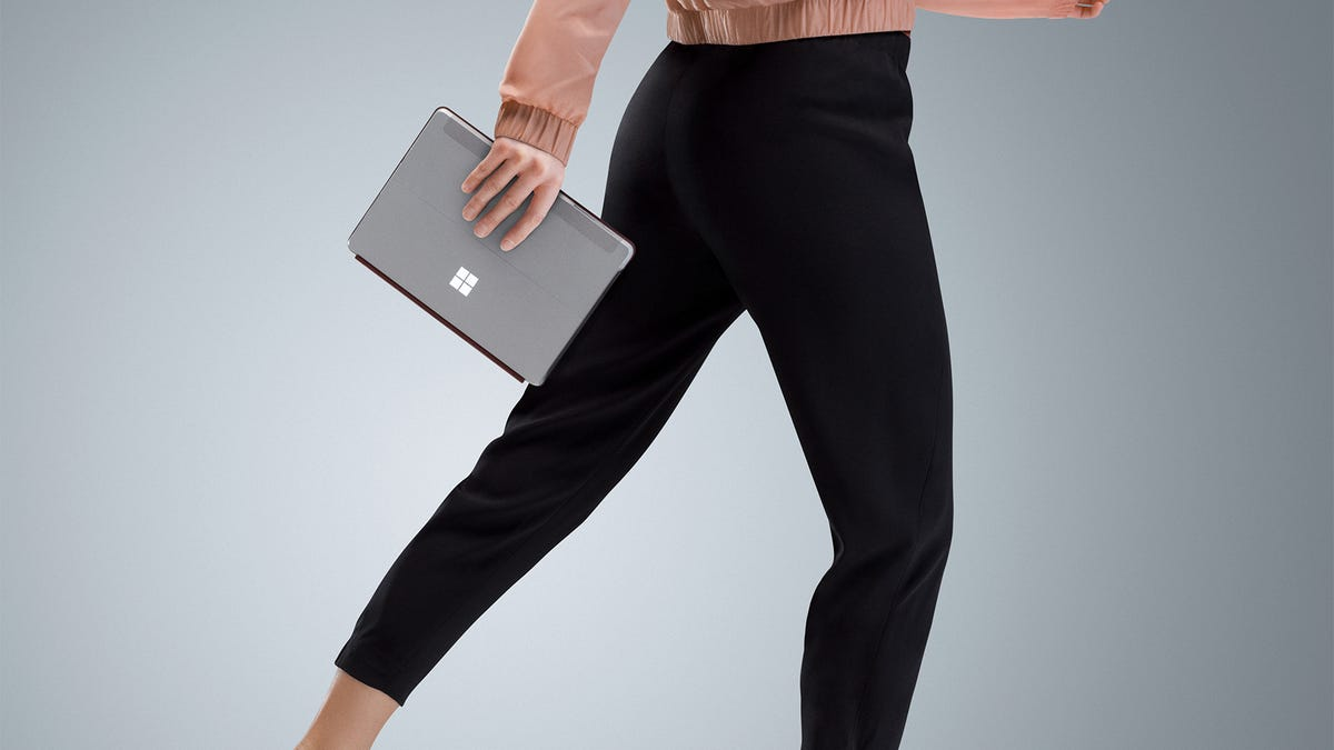 A woman walking with a Surface Go