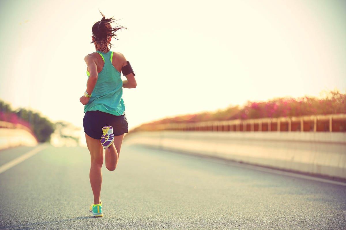 woman running across a city bridge