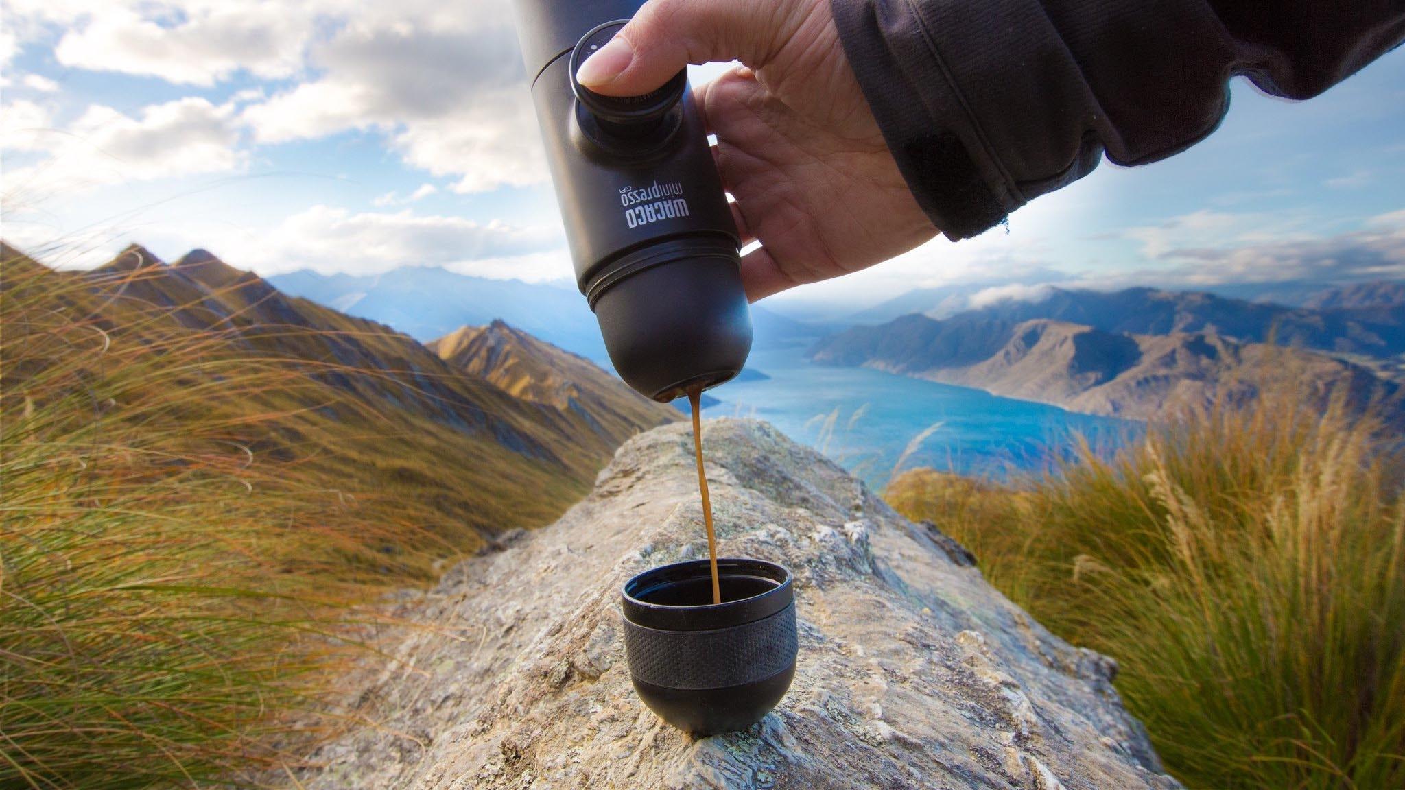 person making espresso coffee on a mountain with wacaco portable espresso maker