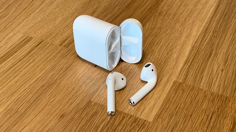Apple AirPods, in front of their case, on a wooden table