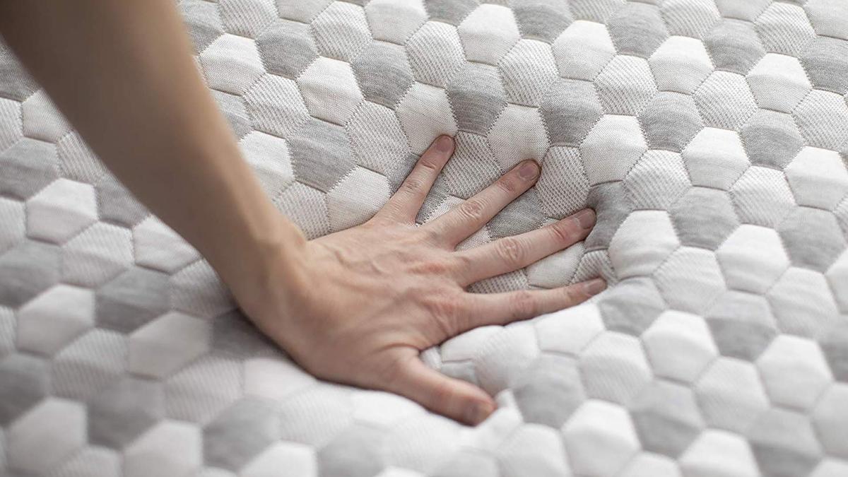 Hand pressing down into a Layla brand mattress