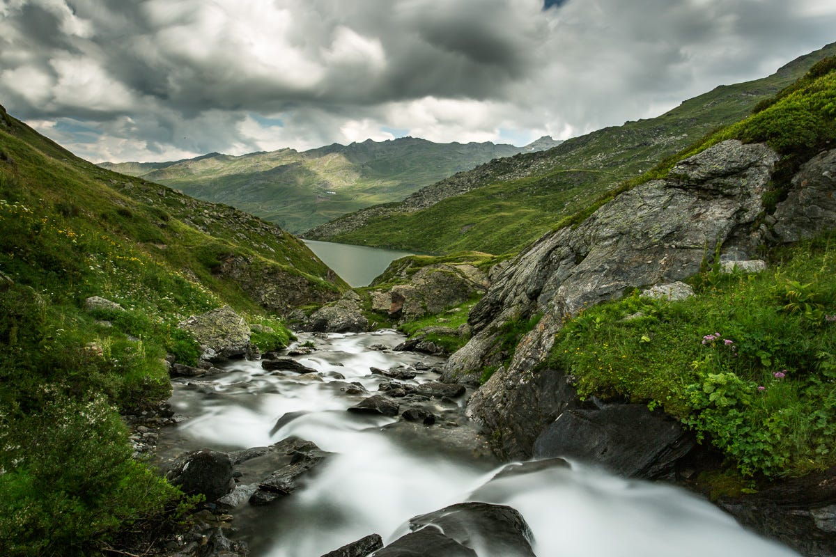 stream flowing down green hills into a lake