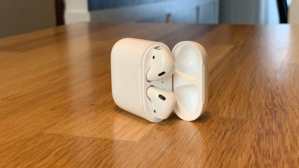 Apple AirPods, in an open case, on a wooden table