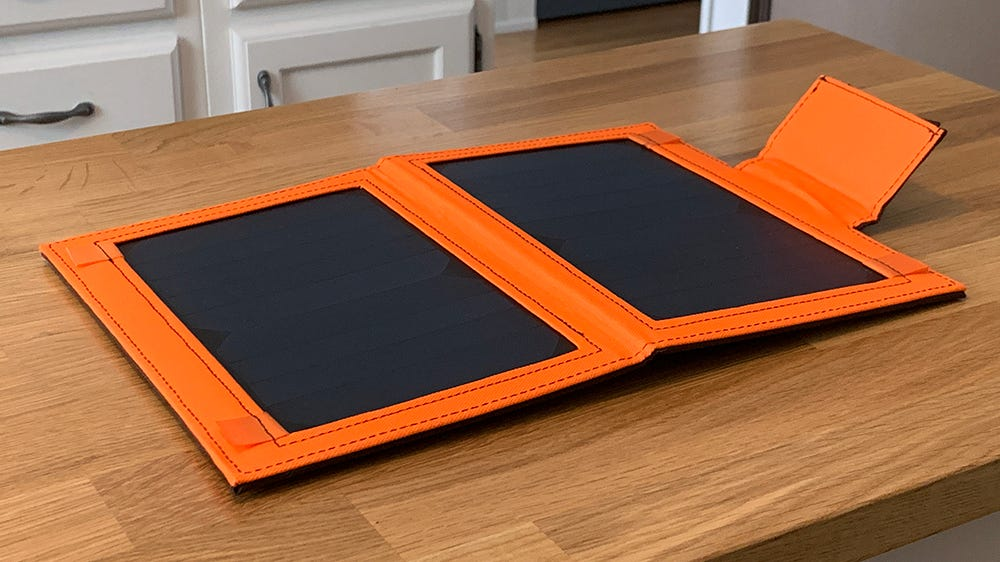 iClever solar charger, open on a wood table