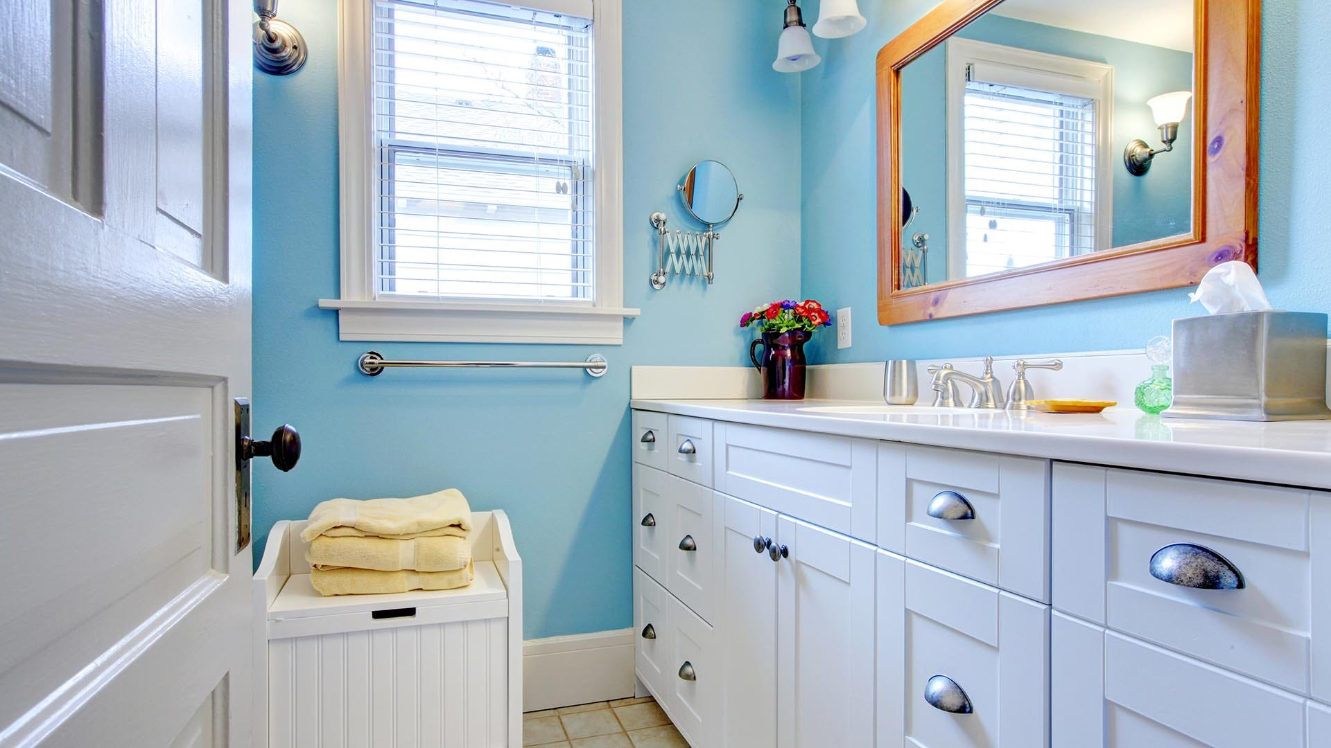 Blue and white bathroom with lots of storage space with open door