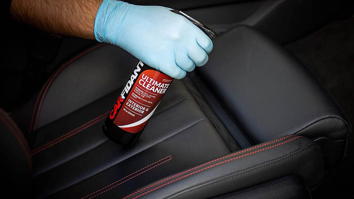 person spraying car cleaner on black leather automotive seats