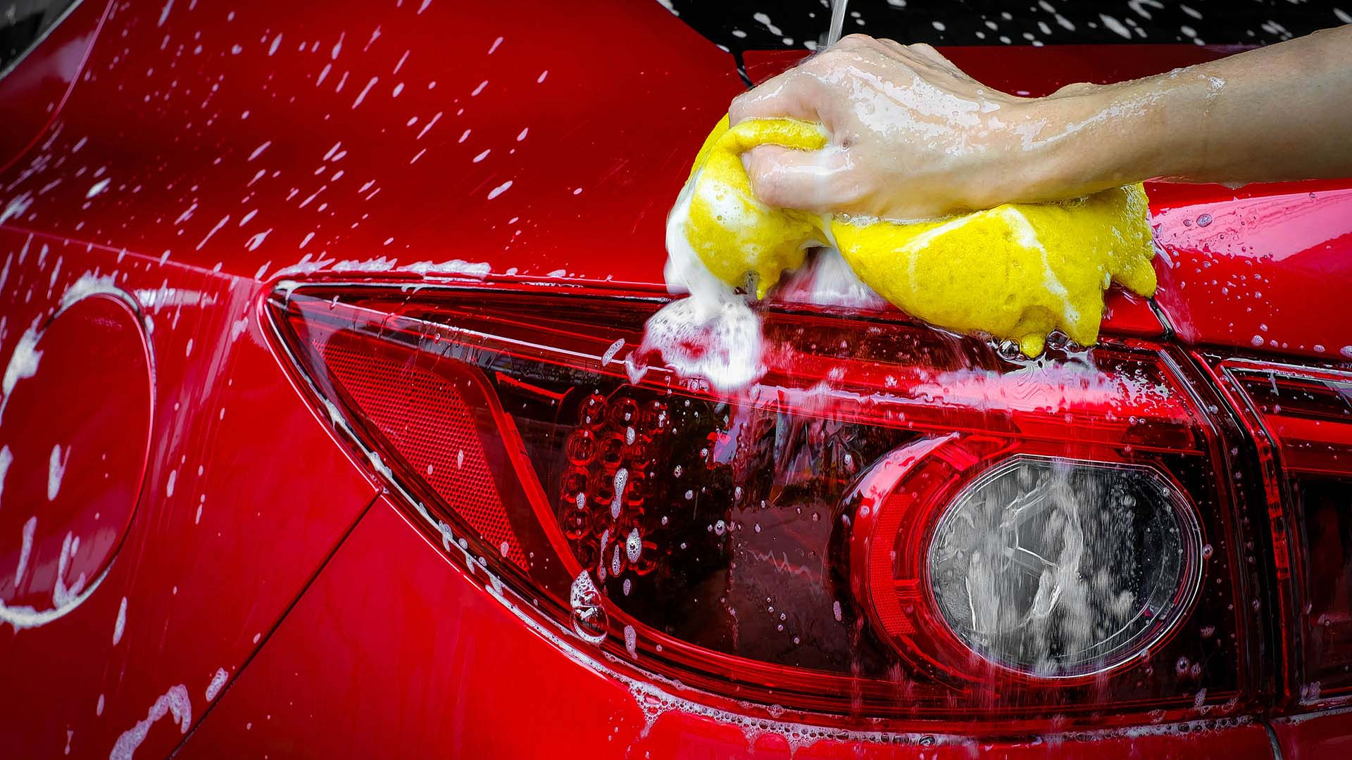 Person washing red car with soapy water and a yellow sponge
