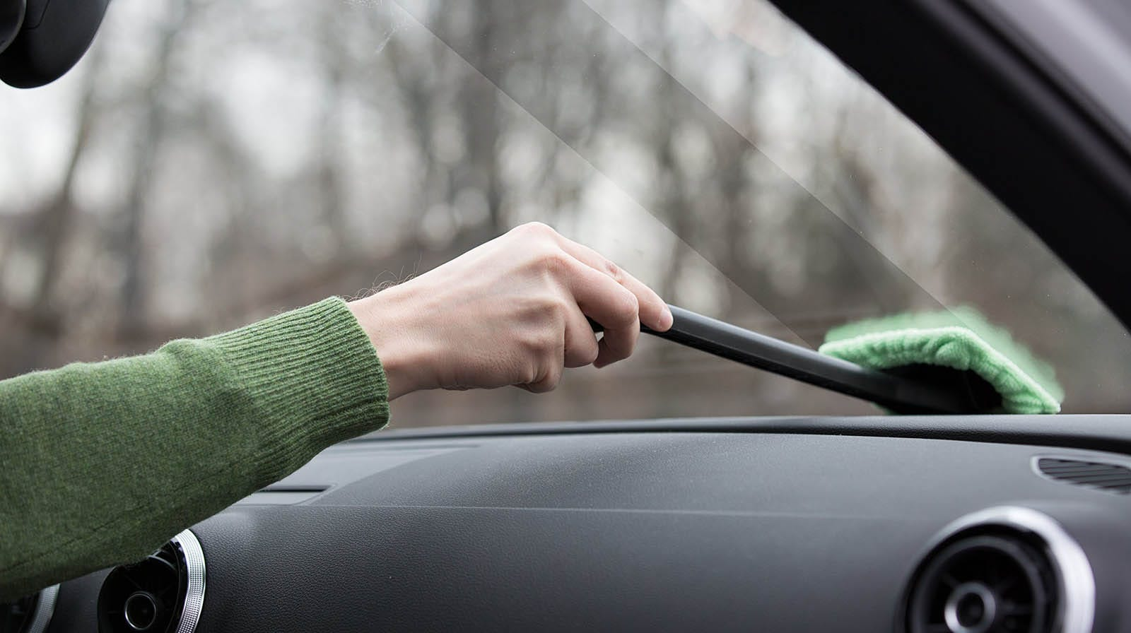 person wiping inside of car windshield with a microfiber EasyWipe cleaner