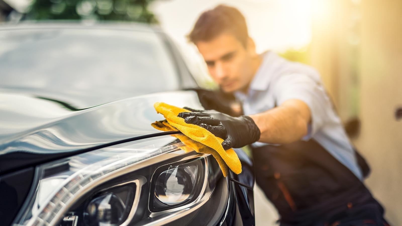 Man polishing a car with microfiber cloth