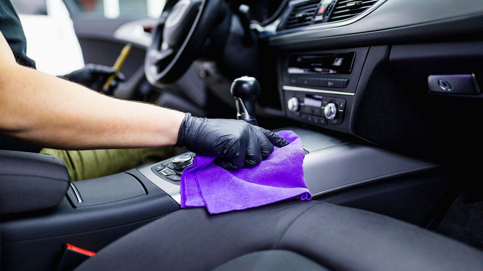 Person wearing nitrile gloves cleaning the interior of a car with a microfiber rag