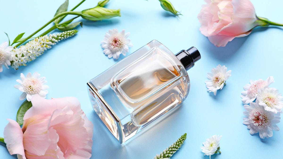 Bottle of perfume on a colorful background, surrounded by flowers
