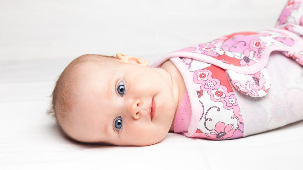 Baby swaddled snugly in a pink and white swaddle