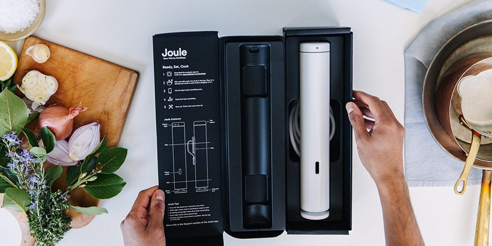 The Joule's packaging, open to display the Joule, on a work surface