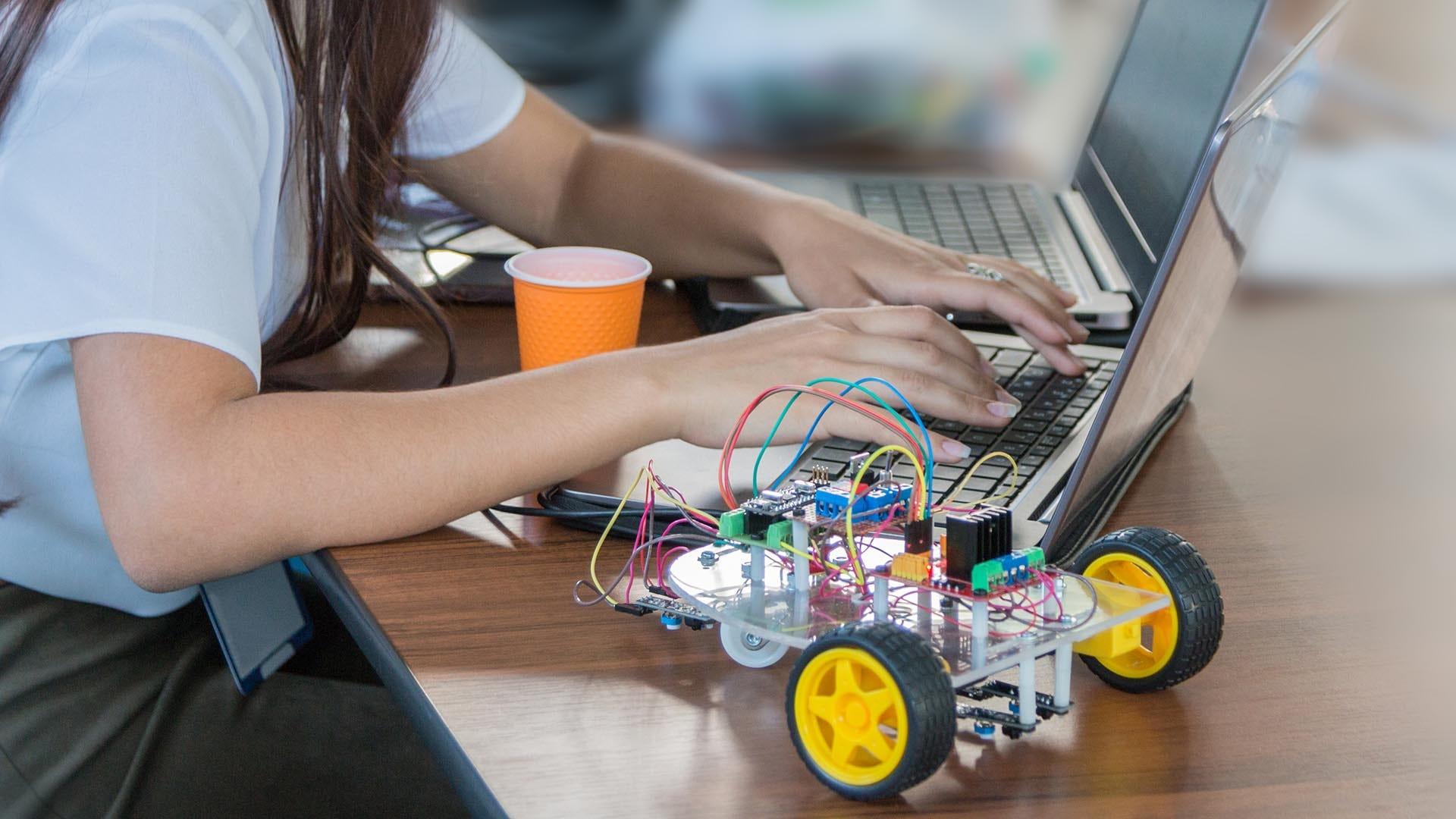 Girl programming a robot using a laptop