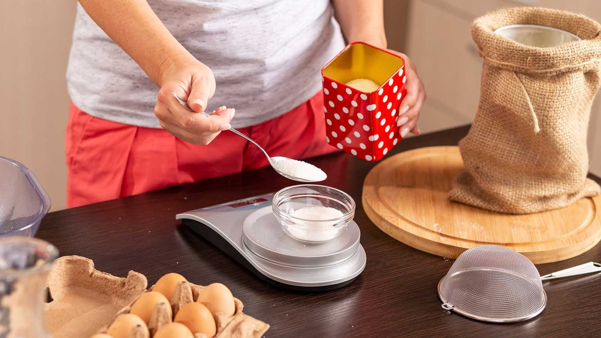 Person measuring sugar with a kitchen scale