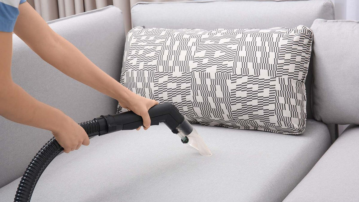 Woman cleaning couch with an upholstery cleaner