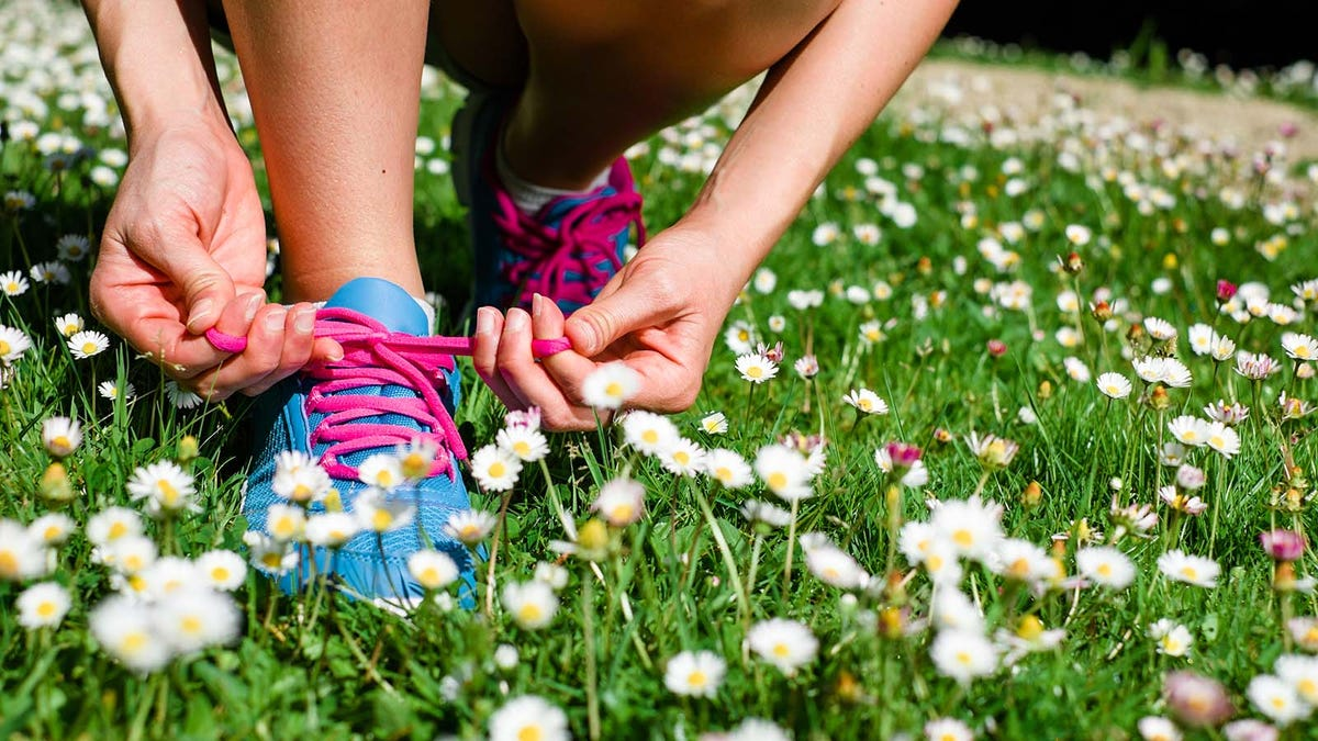 Woman lacing running shoes in a field of daisies