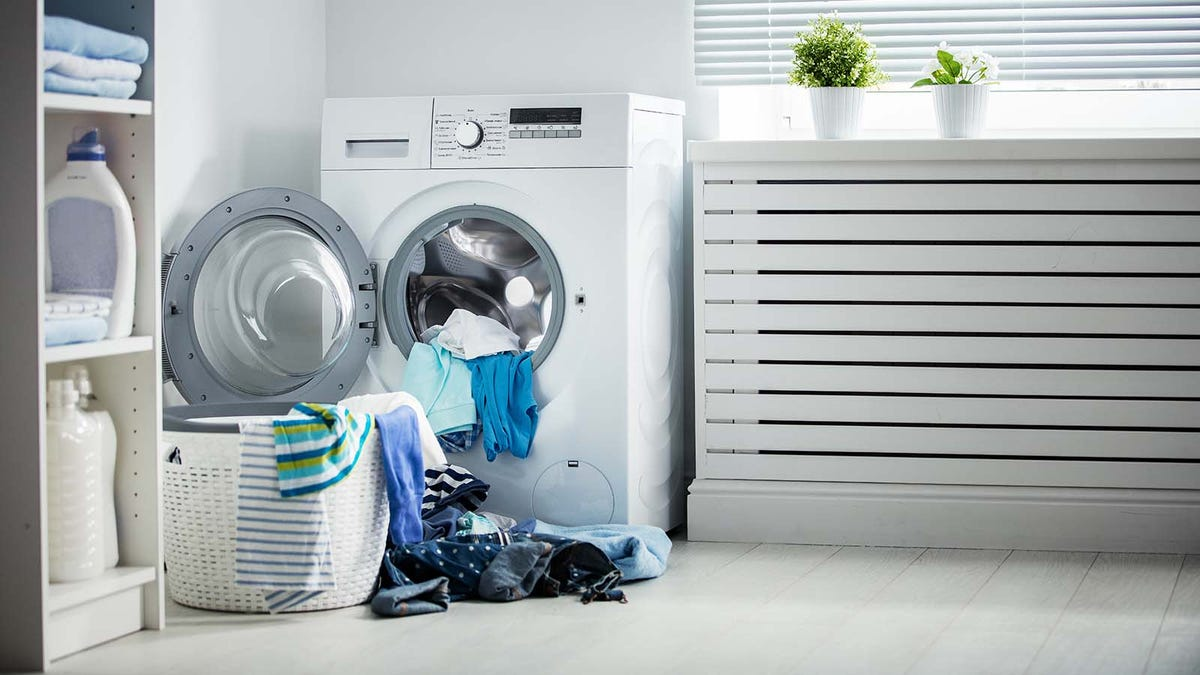 Pile of laundry in front of a washing machine