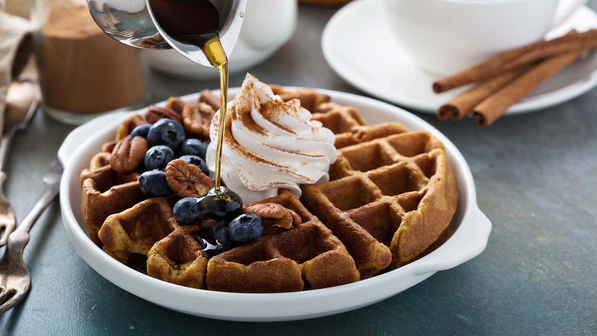 A Belgian waffle with blueberries, nuts, and whipcream