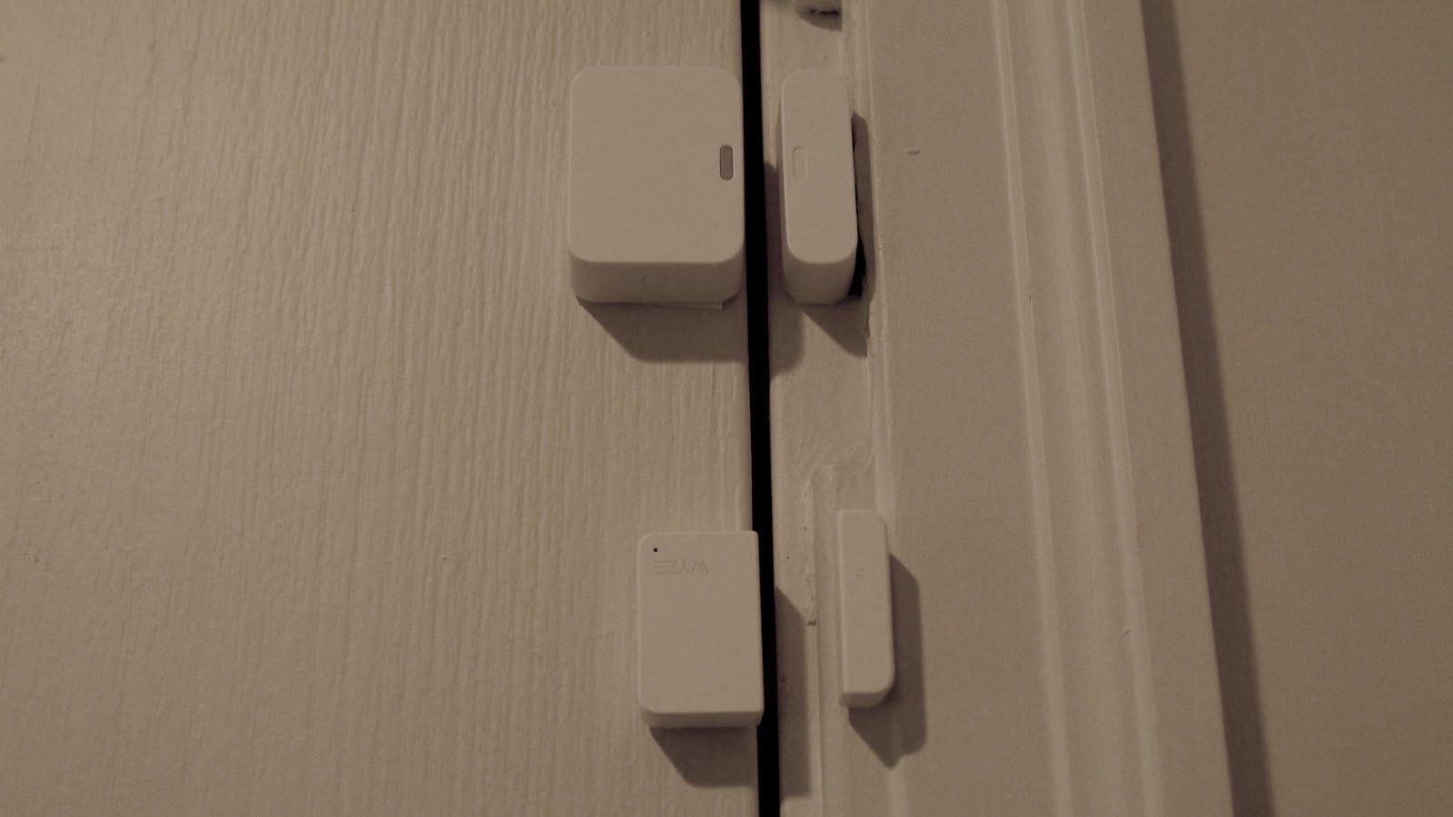 SimpliSafe contact sensor above Wyze Sense contact sense, the latter is about a third smaller.