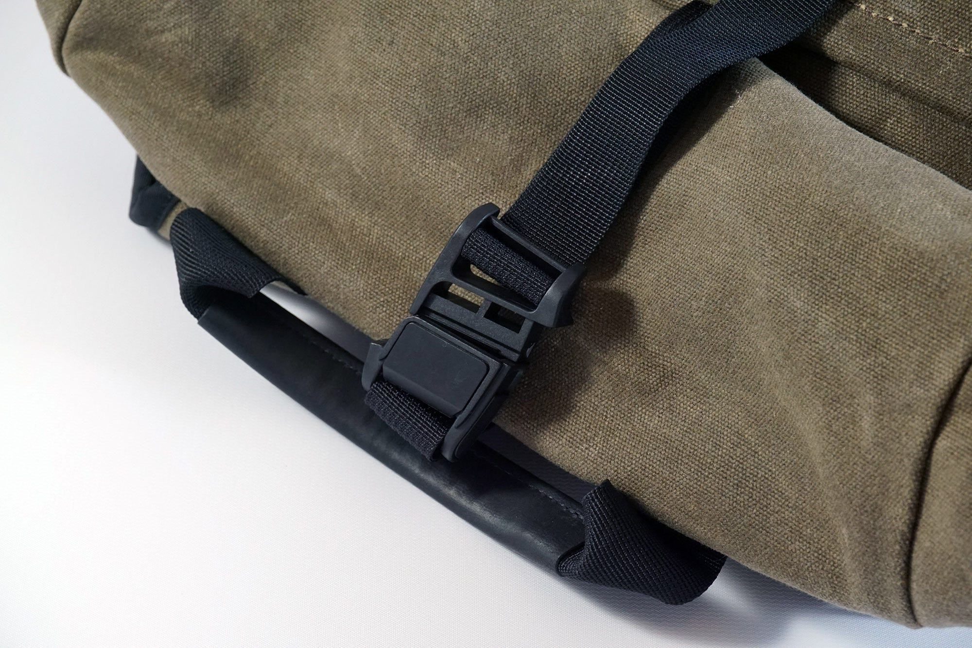 The strap for securing the roll top uses a unique magnetic sliding clasp.