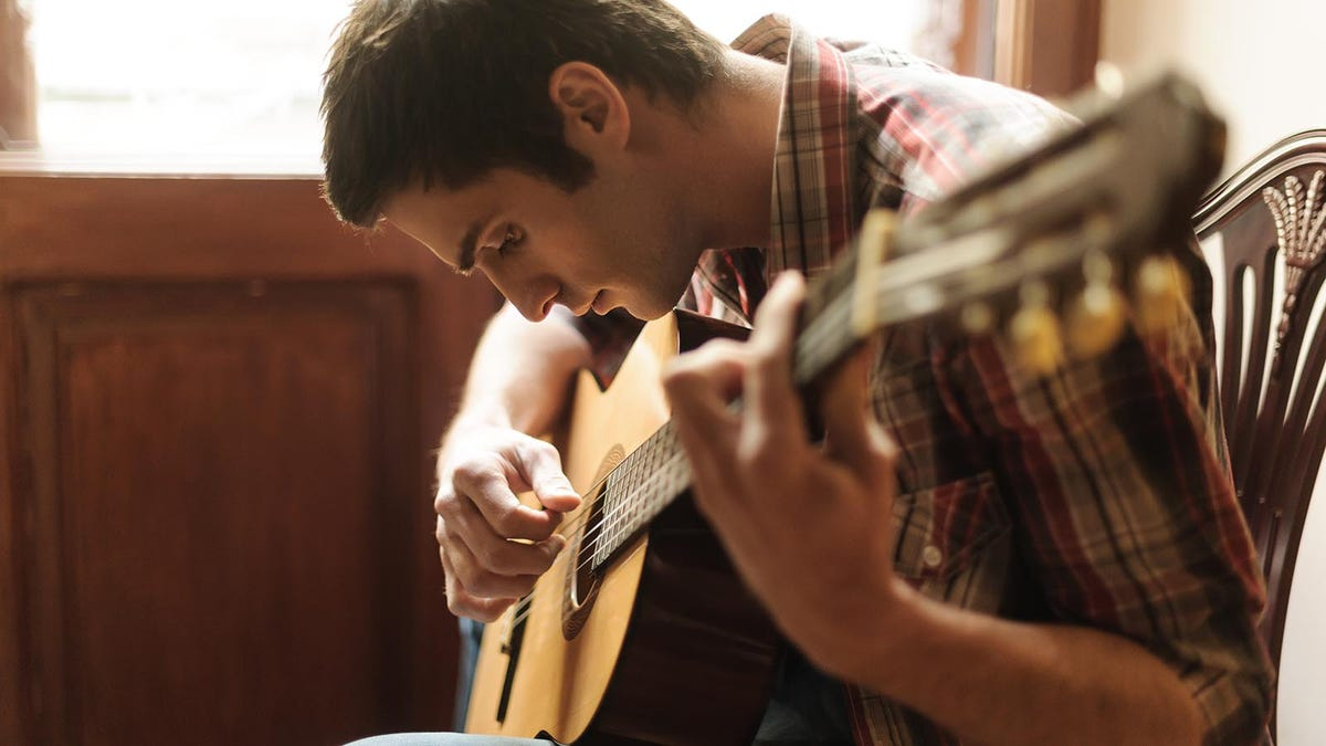 Young man playing an acoustic guitar