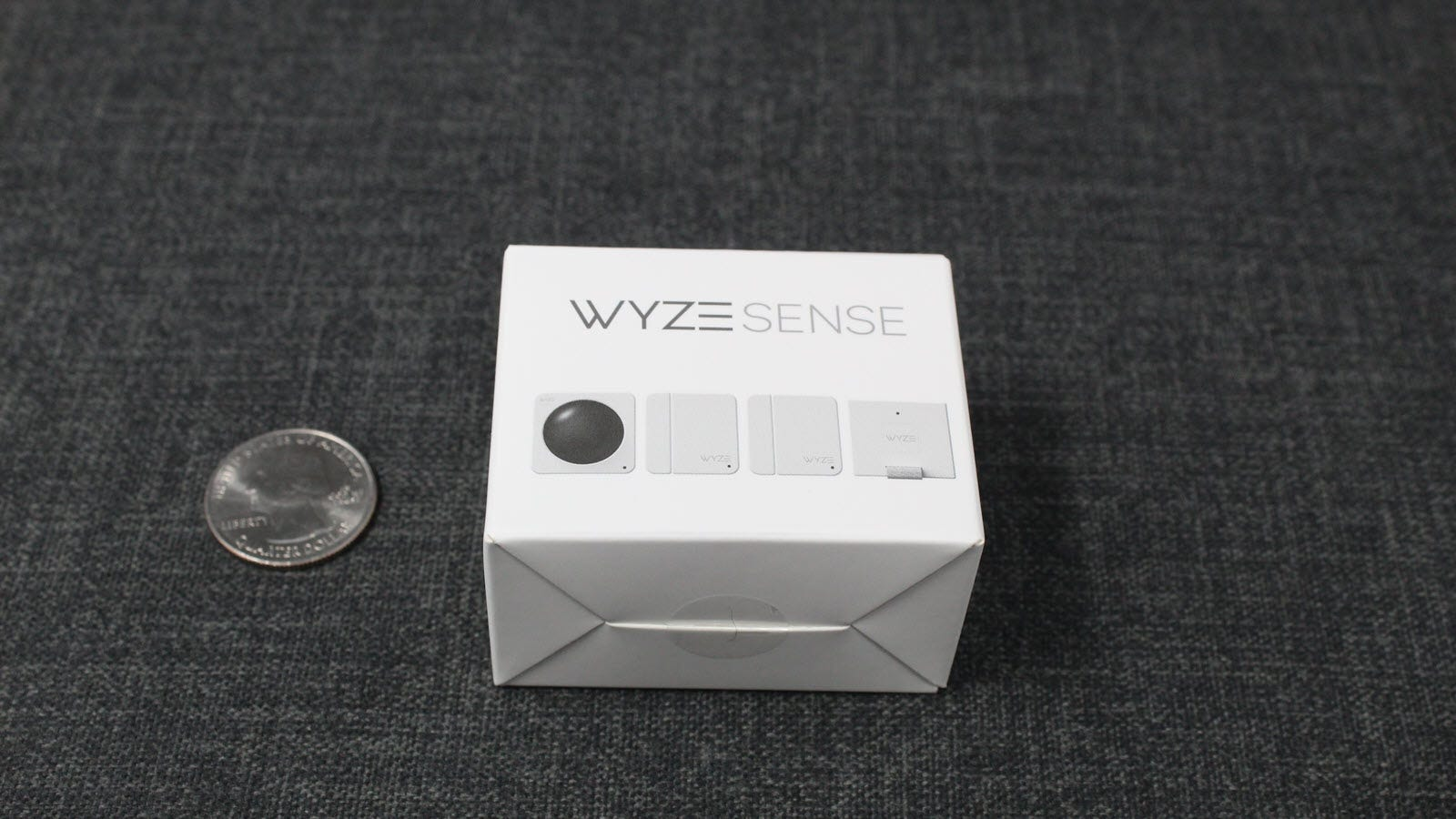 Wyze Sense box next to a quarter, showing how small it is.