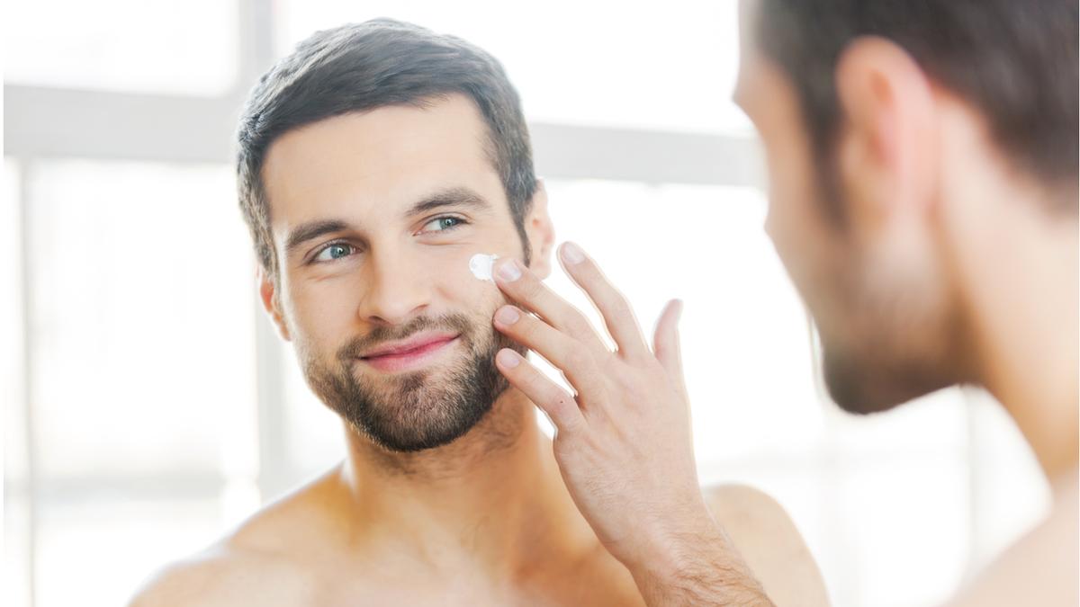 Man applying face moisturizer