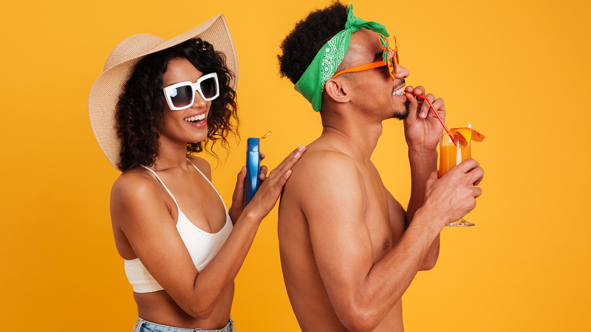 A woman applying sunscreen to a man's back before they hit the beach.
