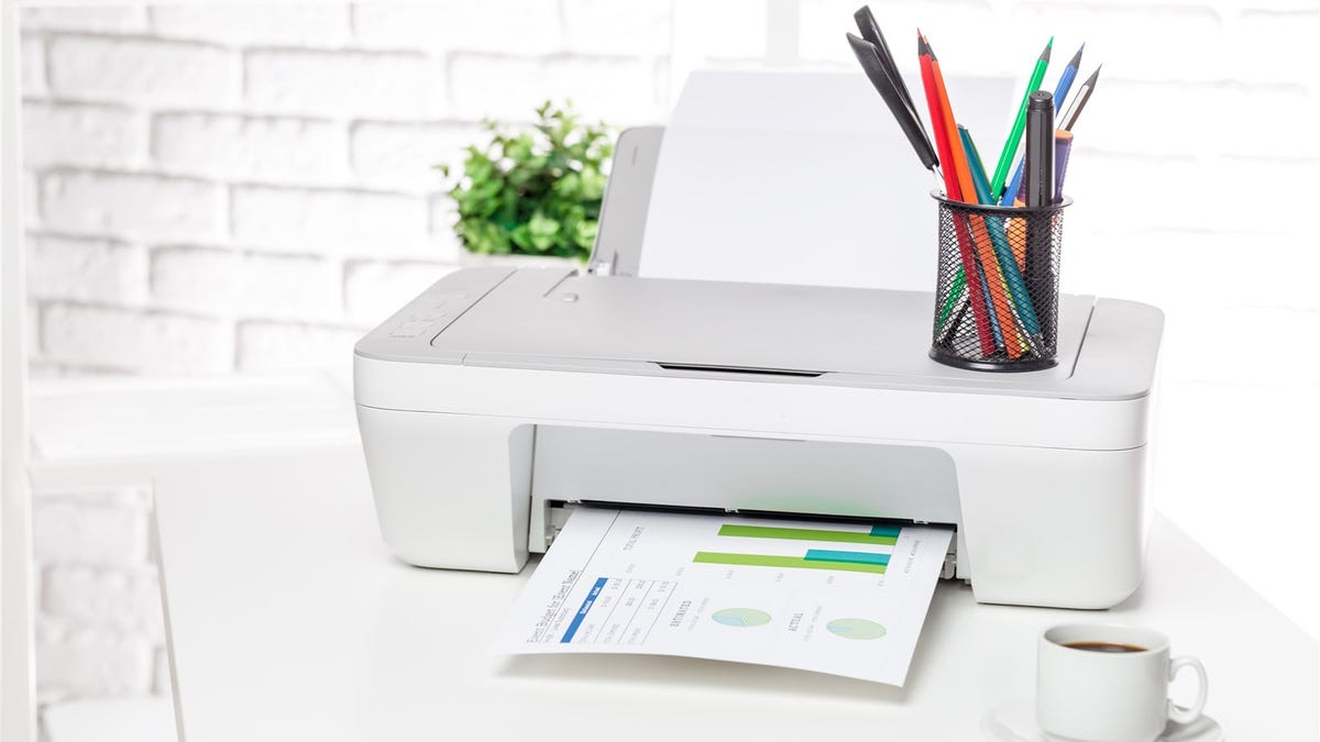 A printer on a table with a cup of pens on top.