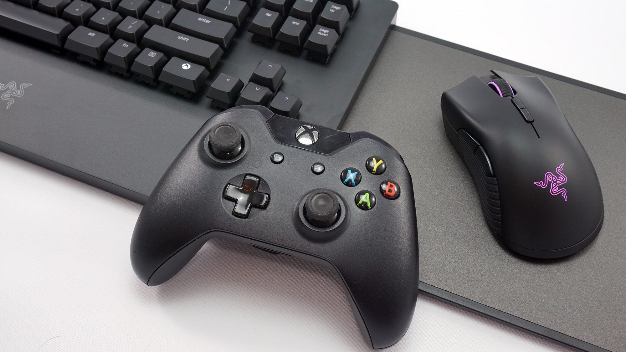 Close-up of the Turret mousepad, mouse, and a game controller with the Turret keyboard in the background.