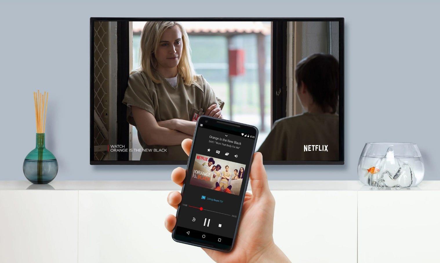 A man's hand holding a phone operating Netflix on a big screen smart TV.