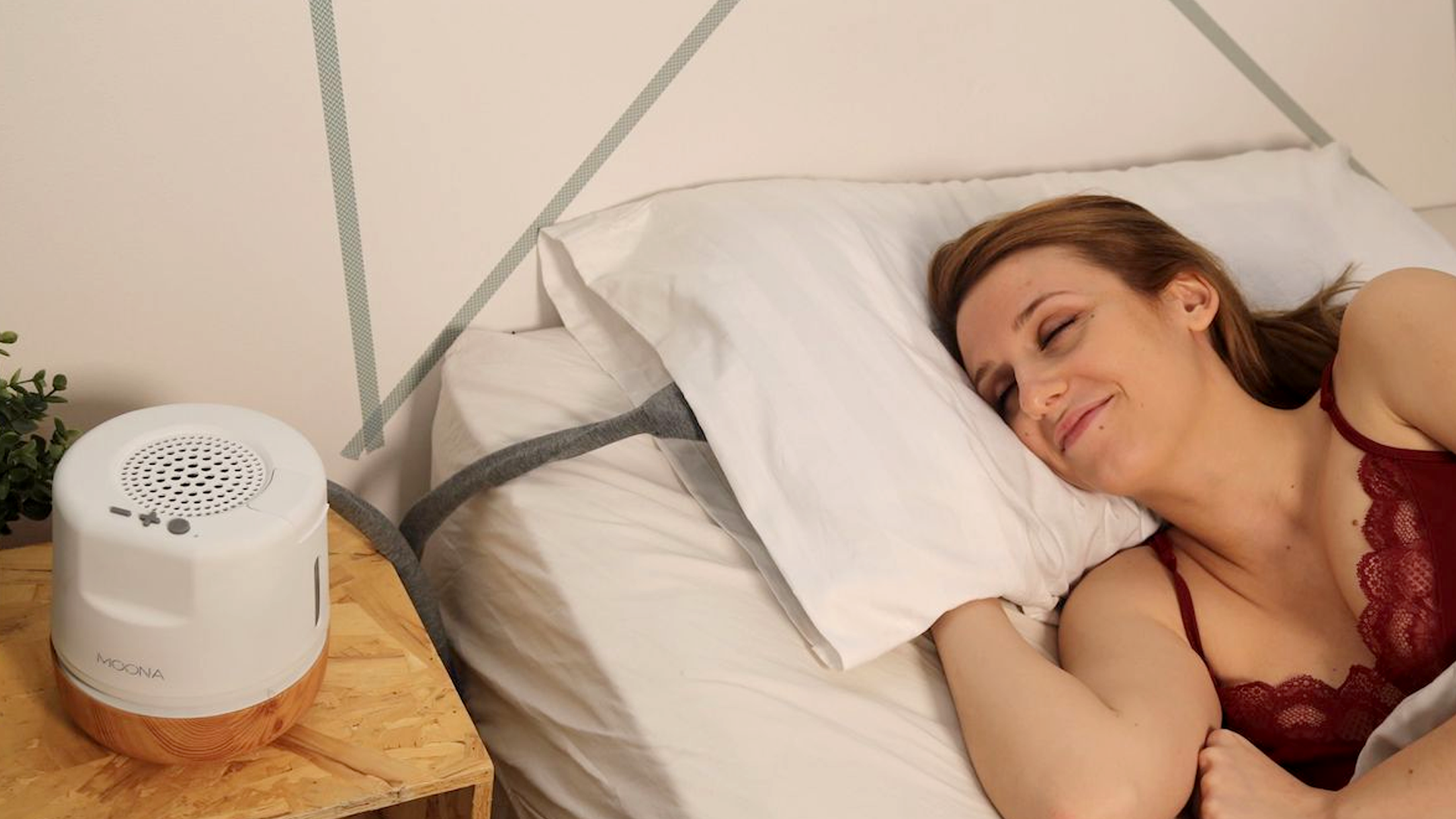 A woman using the Moona smart pillow