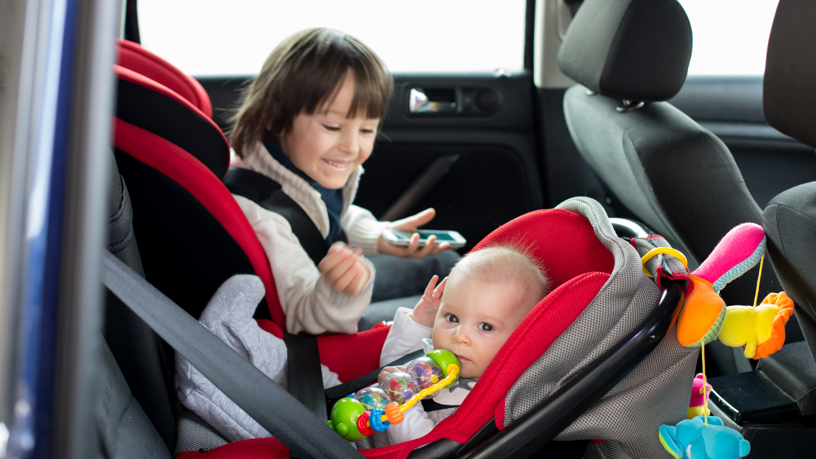 A toddler and a baby in their car seats.