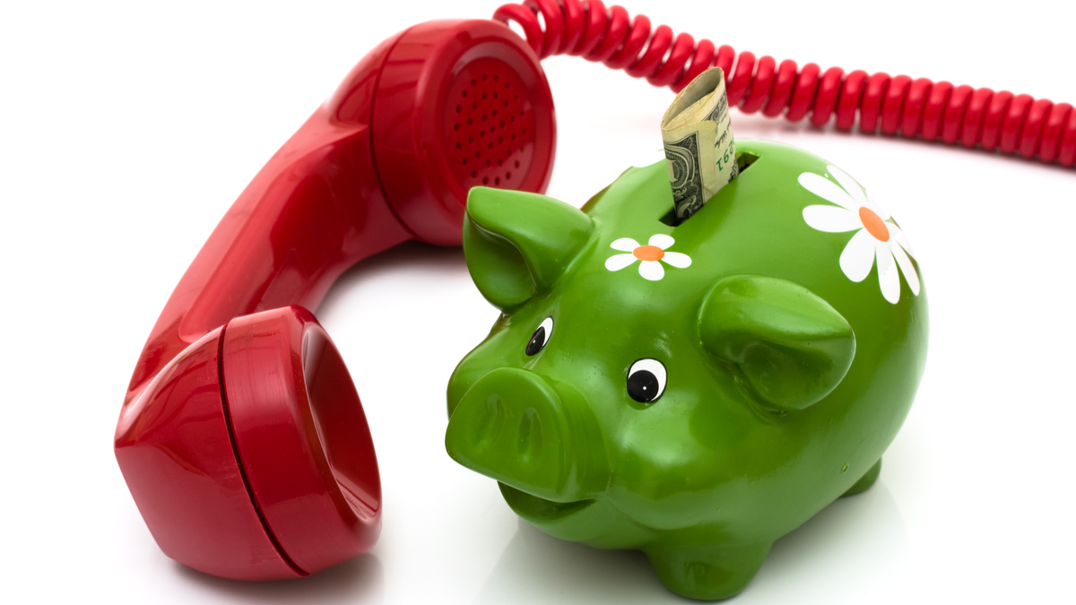 A red corded telephone handset next to a green piggy bank with some cash sticking out the top.