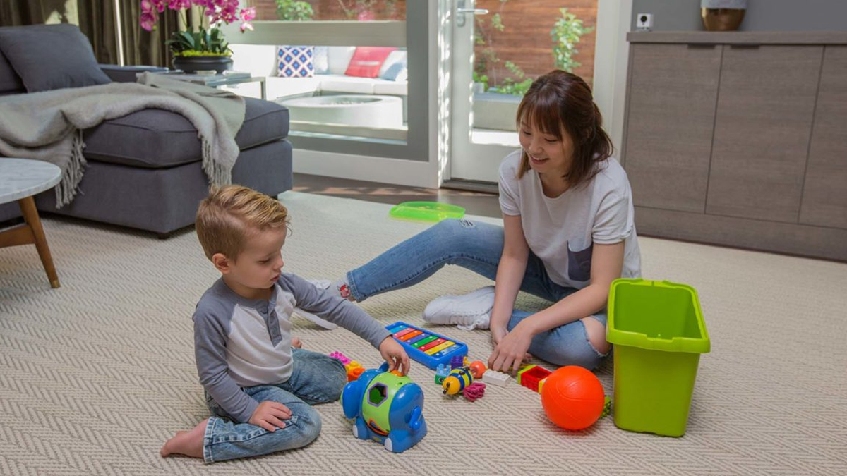 A woman and her son playing in a living room, with a Wyze camera in the background.