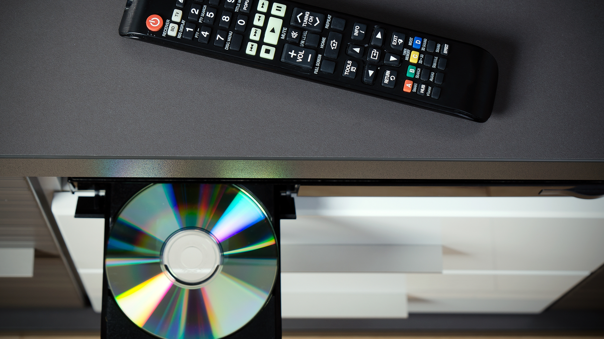 A DVD sitting on the tray in a DVD player, and a remote control on the shelf above.