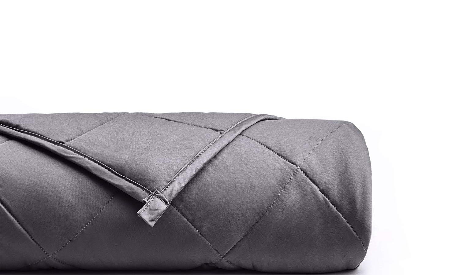 YnM rolled-up, dark gray, weighted blanket.