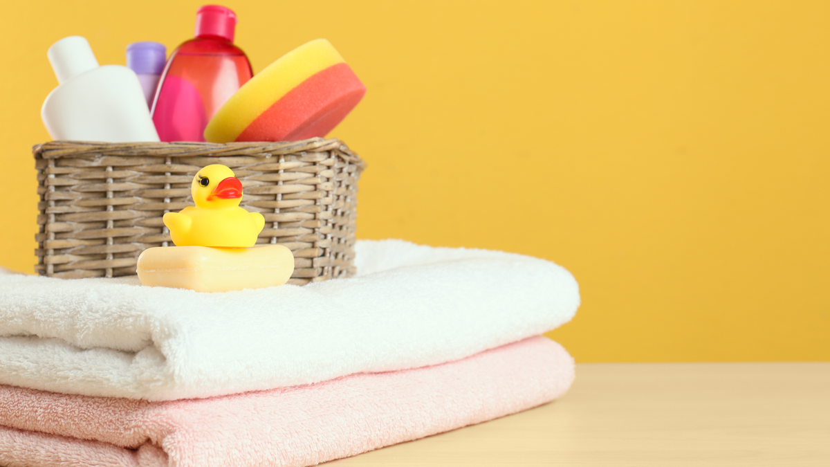 Two folded towels with a a bar of soap, rubber duck, and a basket with bottles of products sitting on top.