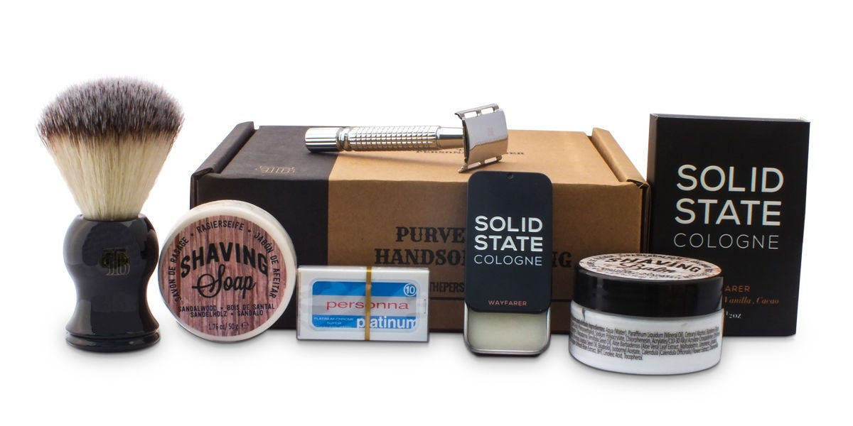 The contents of the Personal Barber subscription box, including a shaving brush, a razor, and containers of shaving soap, Persona Platinum replacement razor blades, Wayfarer Solid State Cologne, and shaving cream.