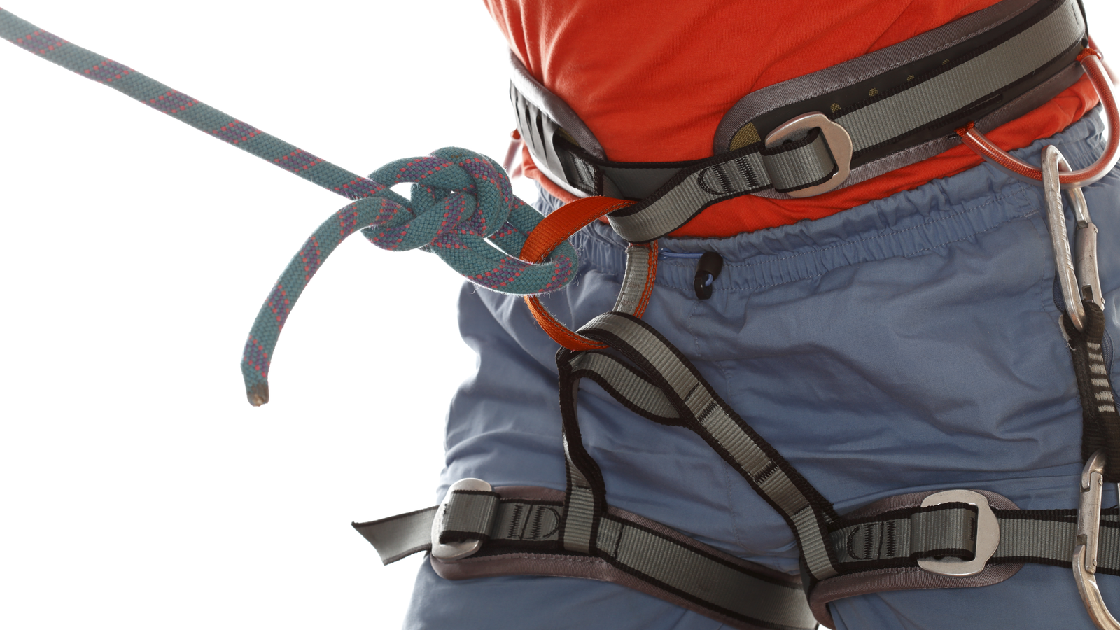 Person wearing a climbing harness that is attached to a rope.