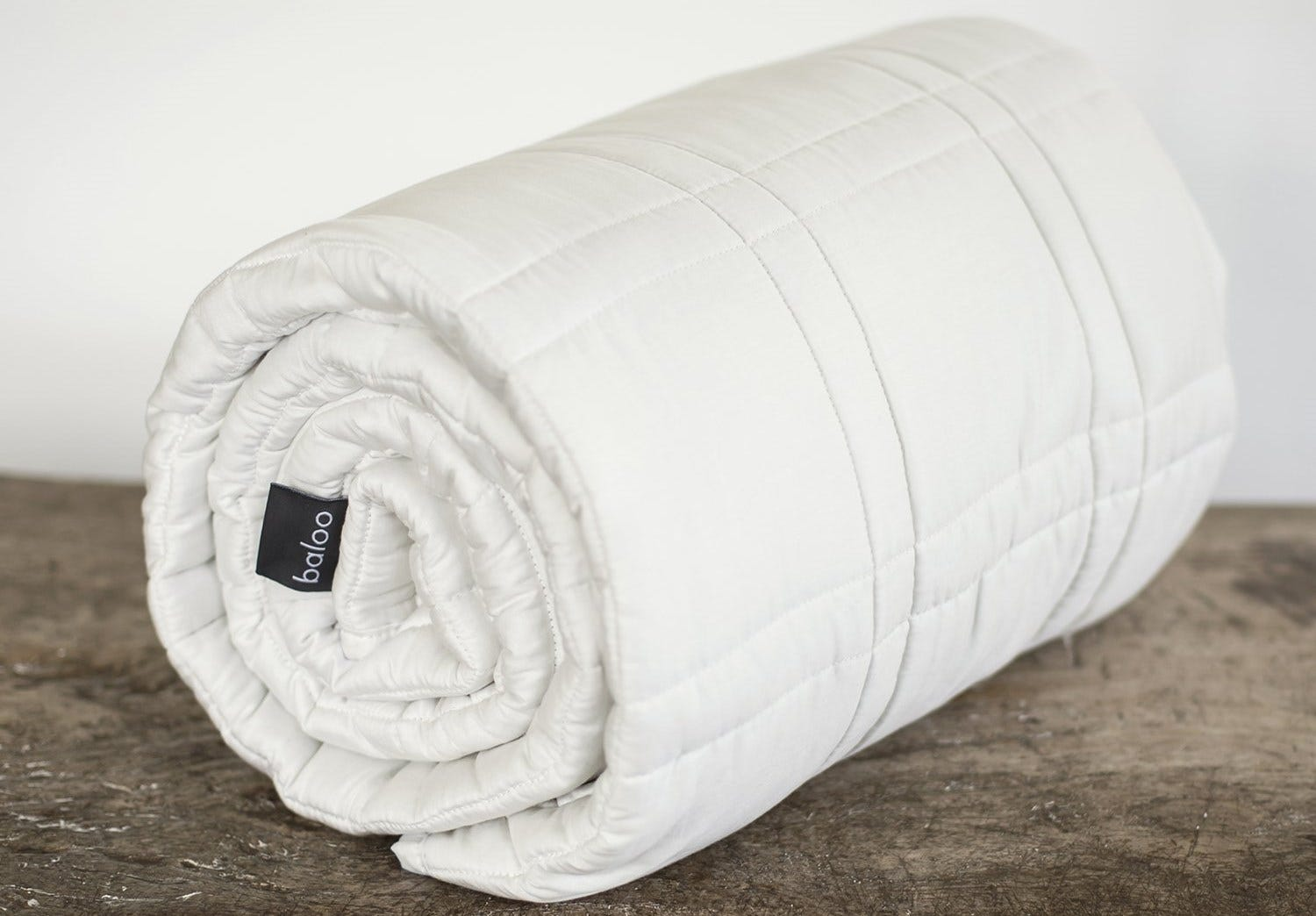 A white, rolled-up Baloo weighted blanket.
