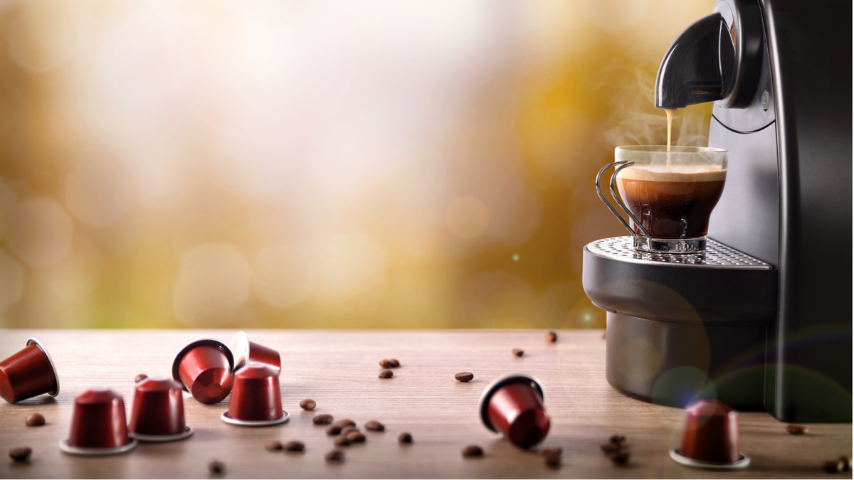 Espresso machine filling a cup with empty K-cups and coffee beans scattered around it.