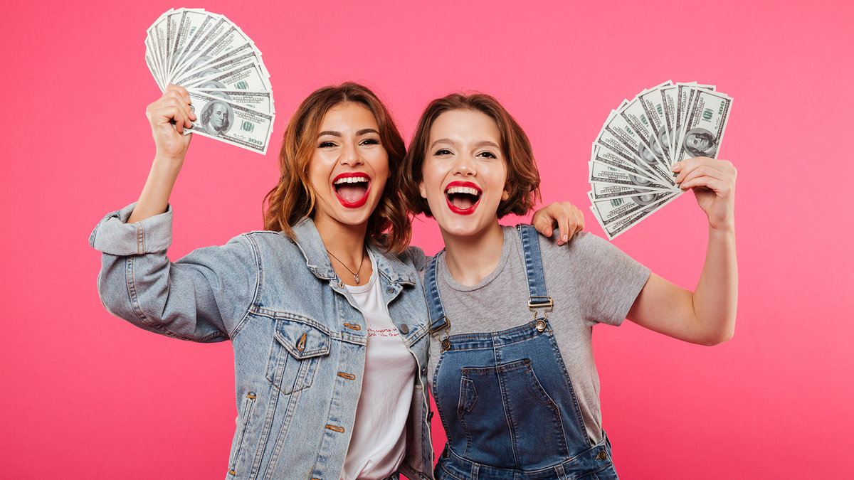 Two young women holding fanned out cash.