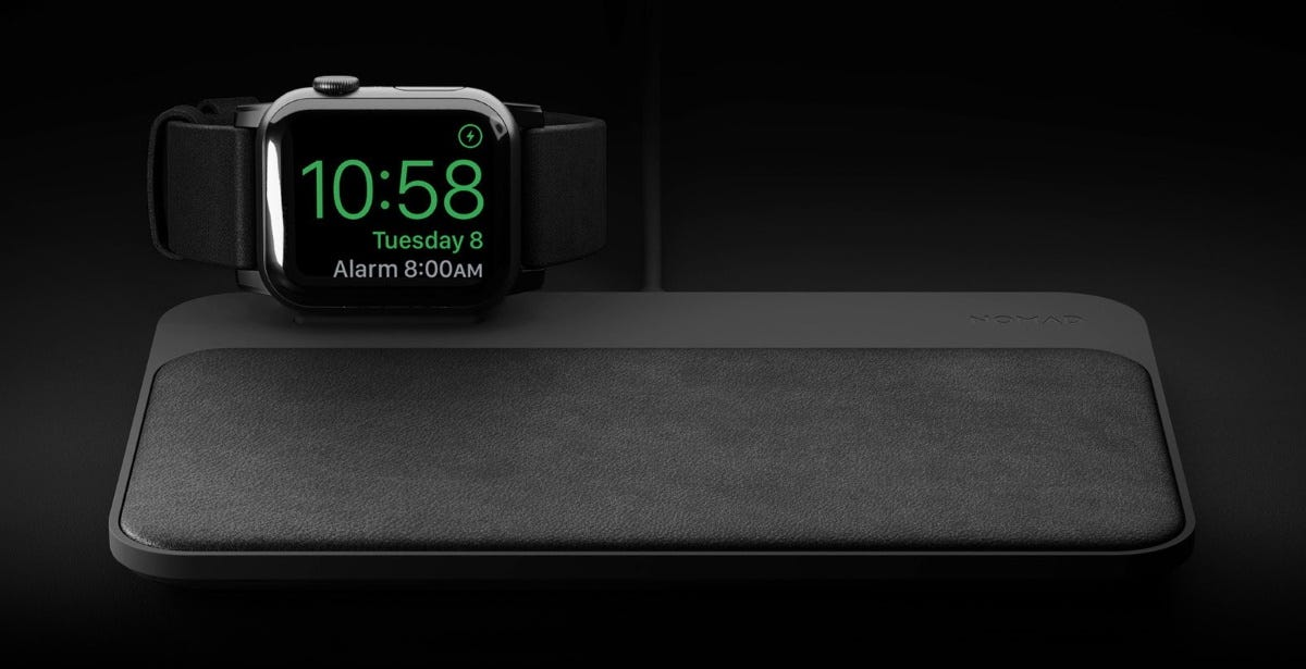 An Apple Watch sitting on a Nomad Base Station wireless charger.