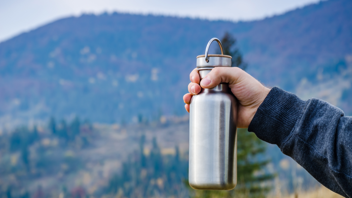 Holding a water bottle in front of a mountain