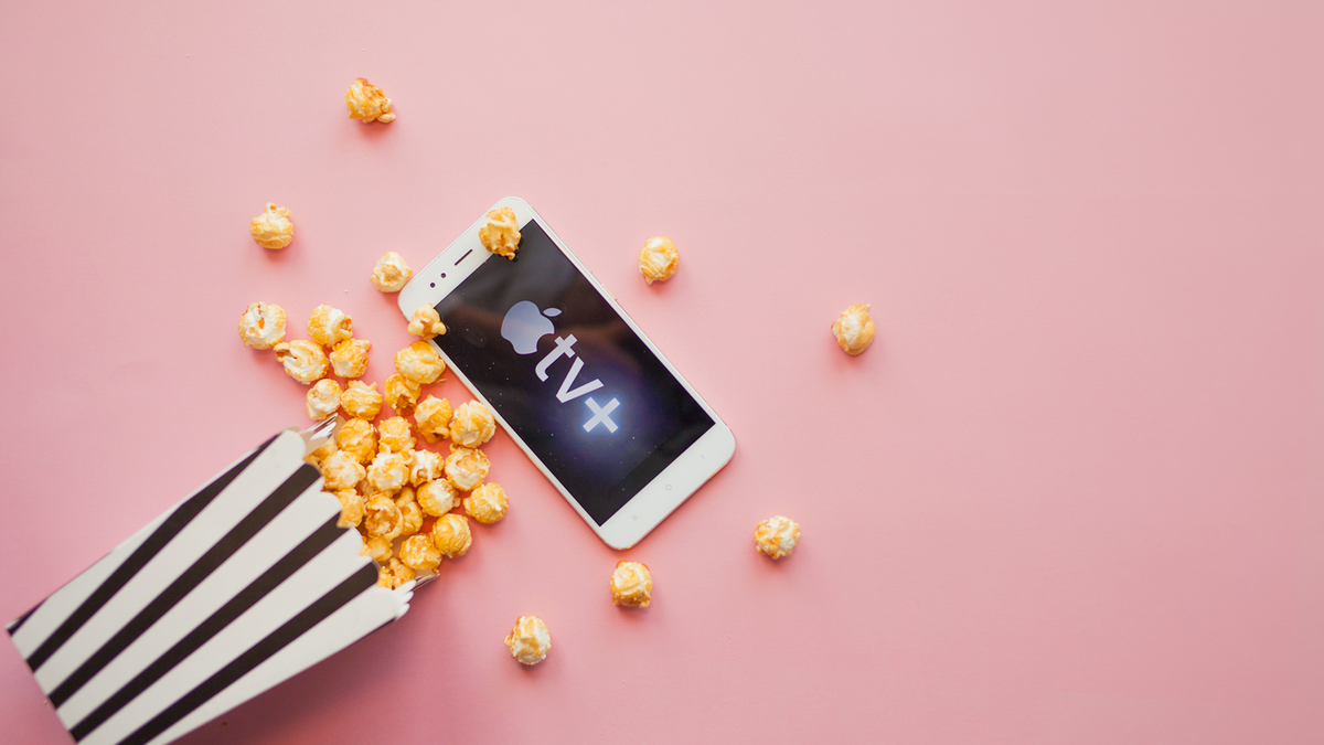 A bag of popcorn spilling onto an iPhone with the TV+ logo.